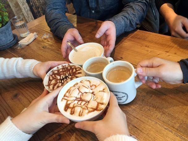 オシャレなカフェでカプチーノや紅茶で乾杯している様子